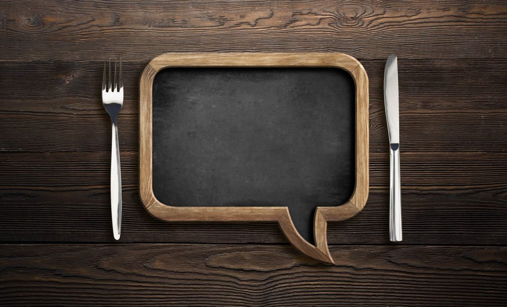 Chalkboard in the shape of a speech bubble next to a fork and knife